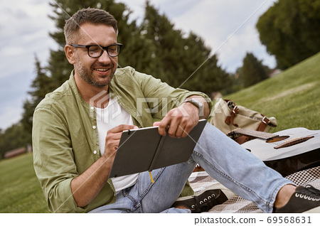 Male musician working in nature. Young creative man wearing eyeglasses sitting on a green grass outdoors and making some notes, acoustic guitar lying near him 69568631