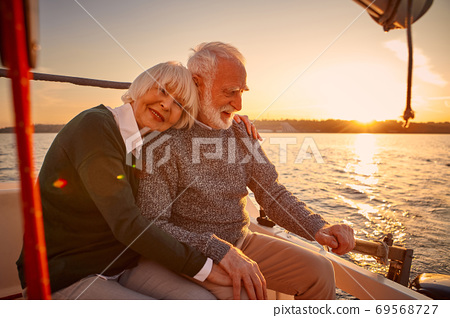 Enjoying sailing at sunset. Happy senior couple, elderly man and woman holding hands, hugging and relaxing while sitting on the side of yacht deck floating in the sea 69568727