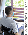 Young man wearing face mask sitting in a wheelchair alone looking out the window 69570677