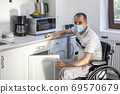 Young man wearing face mask sitting in front of kitchen 69570679