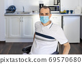 Smiling Young Handicapped Man Sitting On Wheelchair In Kitchen 69570680