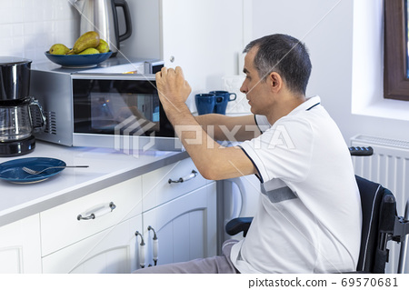 Disabled Man Using Microwave Oven For Baking In Kitchen 69570681