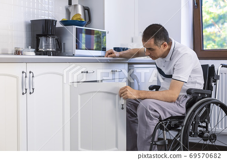 Young Man Sitting On Wheelchair In Kitchen 69570682