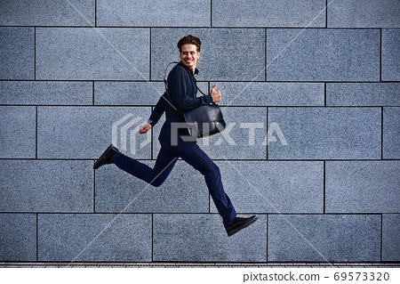 Smiling businessman running fast with briefcase at city 69573320