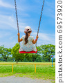 Back view of a girl swinging on a swing in the park 69573920