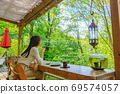 Back view of a woman relaxing in a cafe in nature 69574057
