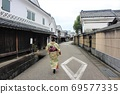Back view of a Japanese woman in a kimono walking through the charming streets of an ancient city 69577335