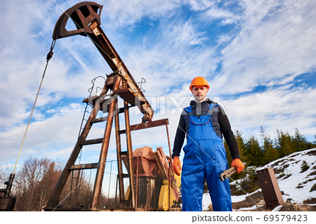 Young oil man standing in front of pump jack. 69579423