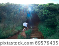 A girl entering a tunnel of overgrown trees in Daimon Park in Keyanooto, Fukuoka Prefecture 69579435