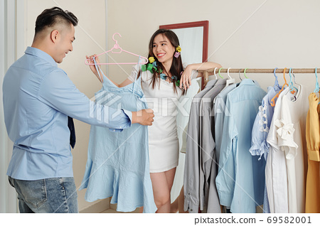 Man helping wife to choose dress 69582001