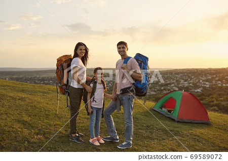 Parents and kid daughter hikers with backpacks are standing looking at the camera on a camping trip in the summer. 69589072