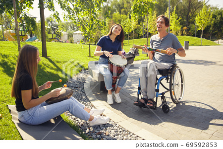 Happy handicapped man on a wheelchair spending time with friends playing live instrumental music outdoors 69592853