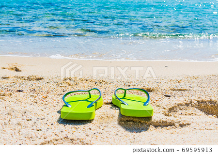 Green flip flops by the sea 69595913
