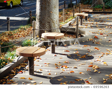 Round bench on the wooden deck of the Jozenji promenade with fallen leaves scattered around 69596263