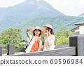 一名年輕女子和一位朋友在女孩出遊期間在由布山的背景下用智能手機射擊[9月] 69596984