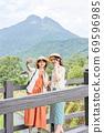 一名年輕女子和一位朋友在女孩出遊期間在由布山的背景下用智能手機射擊[9月] 69596985