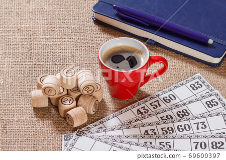 Board game lotto. Wooden lotto barrels, game cards and cup of coffee 69600397