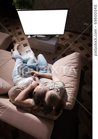Young family of long haired man and woman are lying on the couch and watching TV. The TV screen is cut out white. Mockup and template for designer layout 69600848