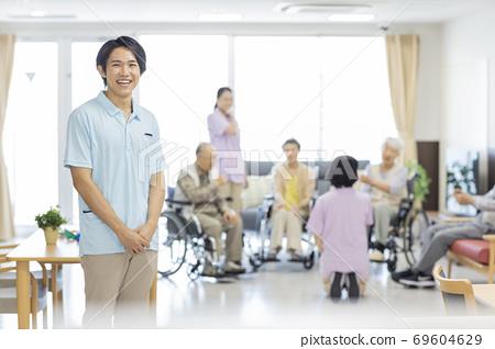 요양 시설에서 일하는 젊은 남성 간병인 노인 홈 69604629