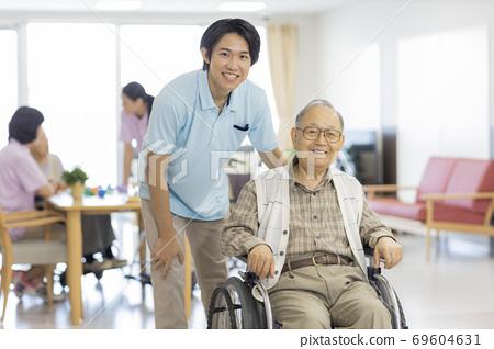 휠체어를 타고 시니어 남자와 간병인 노인 홈 69604631