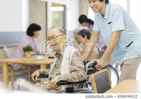 휠체어를 타고 시니어 남자와 간병인 노인 홈 69604632