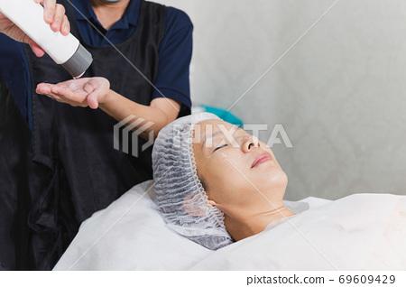 Woman getting face massage treatment at beauty spa salon. 69609429