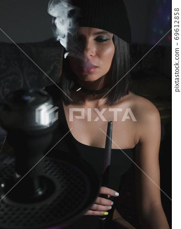 Brunette smoking hookah in dark room 69612858