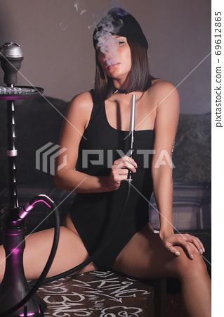 Sensual woman smoking hookah in darkness 69612865