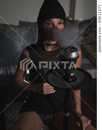 Sensual woman smoking hookah in darkness 69612871