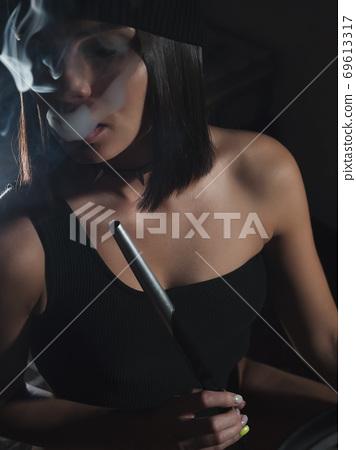 Brunette smoking hookah in dark room 69613317