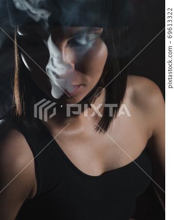 Brunette smoking hookah in dark room 69613322