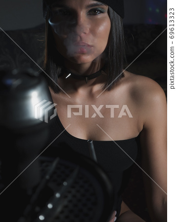 Brunette smoking hookah in dark room 69613323