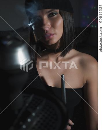 Brunette smoking hookah in dark room 69613388