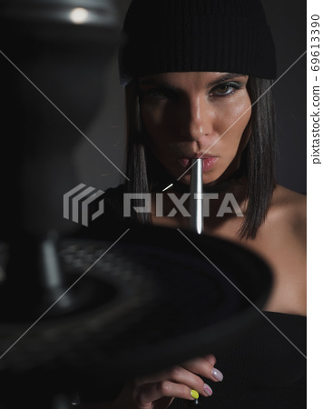 Brunette smoking hookah in dark room 69613390