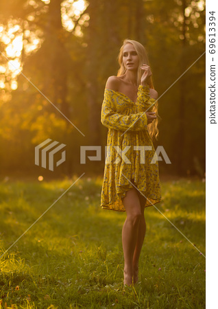 Blond woman resting in forest at sunset 69613394
