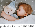 Little baby girl sleeping with her bear toy. 69613461