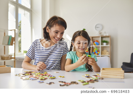 Mom and little daughter put together puzzles while sitting at a table in the room. 69618483