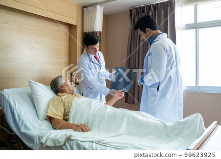 Doctor holding an X-ray film for an infected patient. 69623925