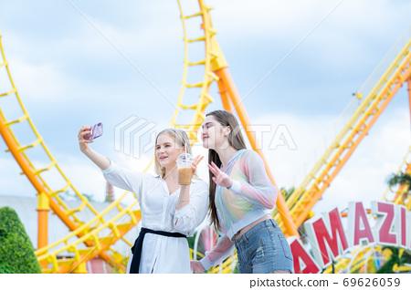 Two cheerful teenage friends taking selfie. 69626059