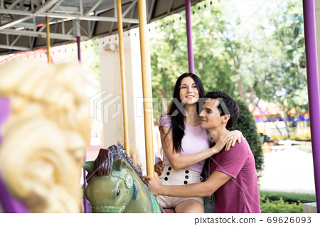 Couples play carousel while visiting. 69626093