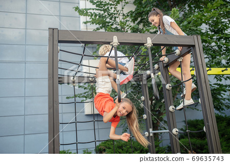 Kids climbing on outdoor playground and looking excited 69635743