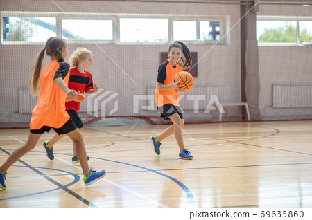 Kids in bright sportswear playing basketball together and running 69635860