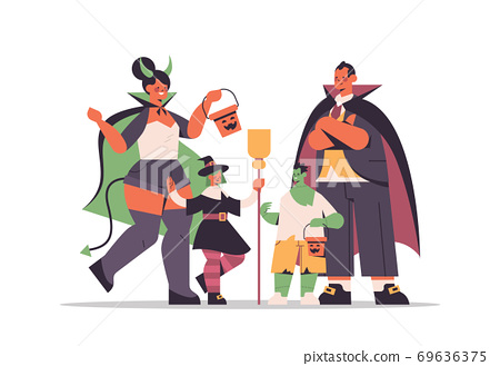 parents and cchildren in different costumes standing together happy halloween party celebration concept 69636375