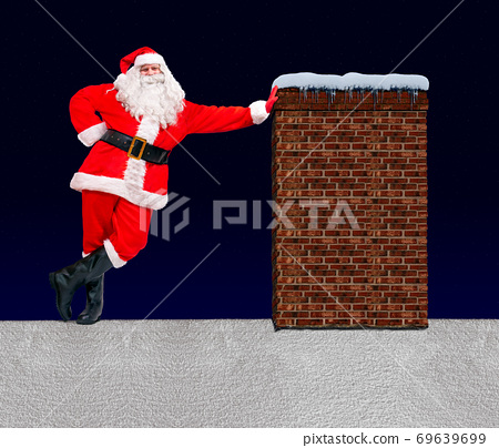 Santa Claus is lean about the chimney at a snowy roof on a background of dark blue with stars. 69639699
