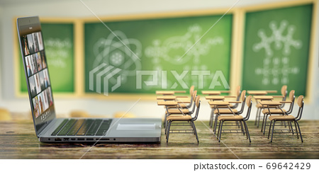 Online education and e-learning concept. Home quarantine distance learning. Laptop and school desks on blackdesk in classroom background. 69642429
