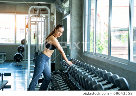 Fitness woman exercising lifting dumbbells at modern Gym,Fitness. 69643358