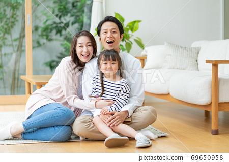 一家三口坐在客廳地板上的肖像 69650958