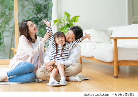 A girl sitting on the floor of the living room and frolicking, and mom and dad watching over it 69650985