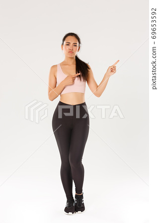 Full length of skeptical, disappointed asian fitness girl, sportswoman smirk and sulking while complaining on bad gym or awful workout gear, pointing upper right corner displeased, white background 69653592