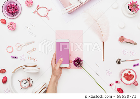 Smartphone in woman hand above artist workplace 69658773